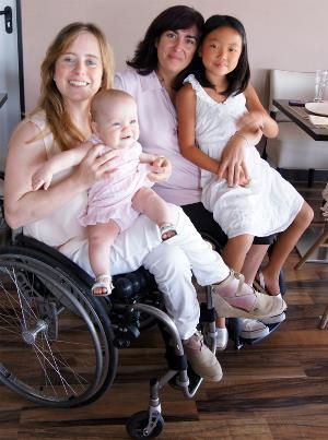Dos madres en silla de ruedas con sus hijas