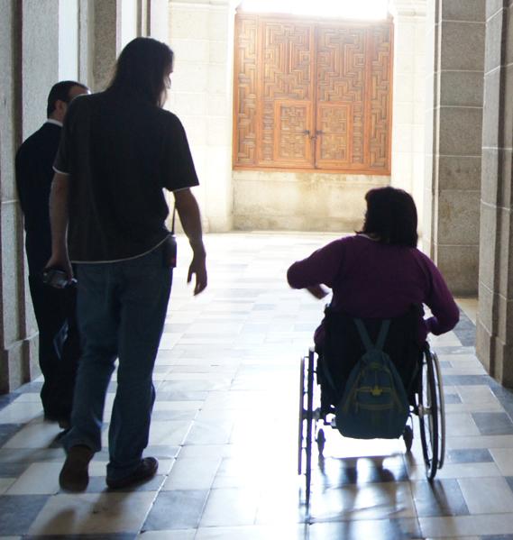 Mujer en silla de ruedas acompañada por dos personas más