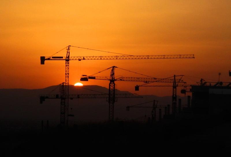 Grúas de construcción a contraluz sobre la imagen de un atardecer