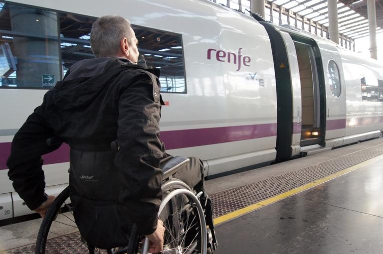 Una personas en silla de ruedas se dirige a un tren de Renfe