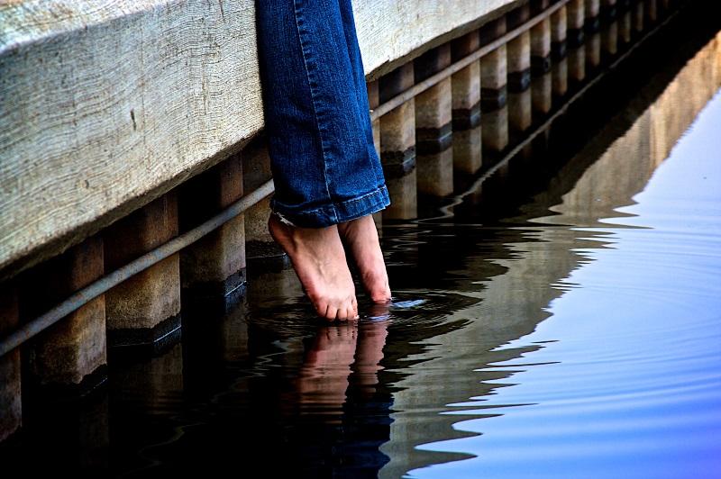 Detalle de las piernas de una mujer en vaqueros metiendo los dedos de los pies en el agua