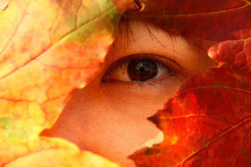 Detalle de una mujer ocultándose bajo hojas de otoño