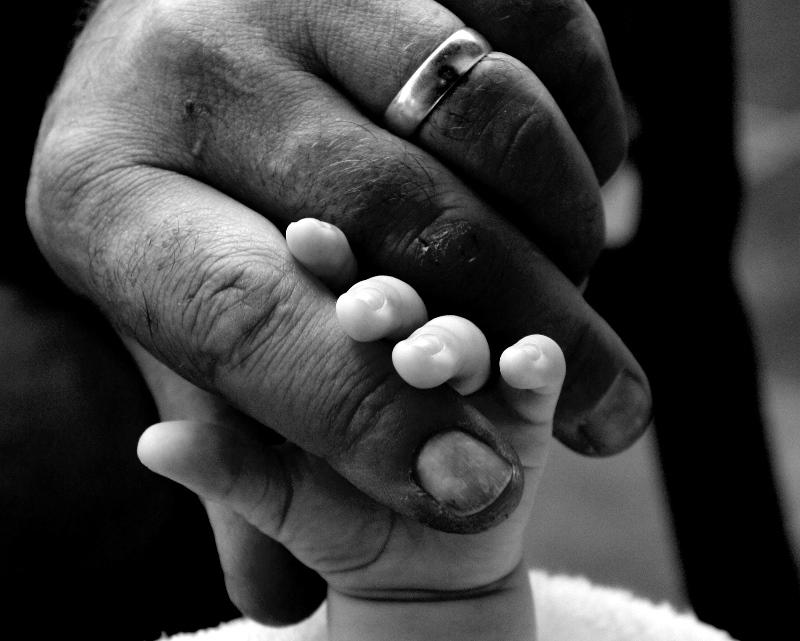 Detalle de la mano de una padre sosteniendo la de su hijo