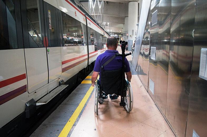 Un usuario de silla de ruedas pasa por un estrecho pasillo de un andén de Cercanías, en Atocha