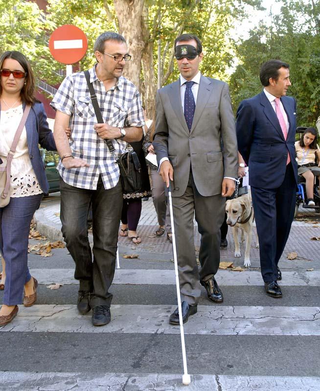 El consejero de Asuntos Sociales de la Comunidad de Madrid, Salvador Victoria, con los ojos taapdos cruzando un paso de peatones