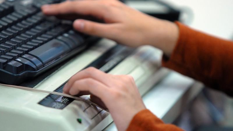 Unas manos escribiendo a máquina y con teclado especial para ciegos