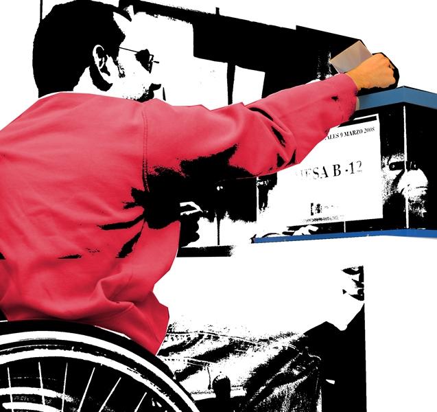 Un hombre en silla de ruedas introduce un voto en una urna