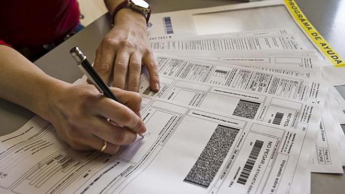 Una persona rellena el formulario de la declaración de la renta (imagen de la web de Plena Inclusión)