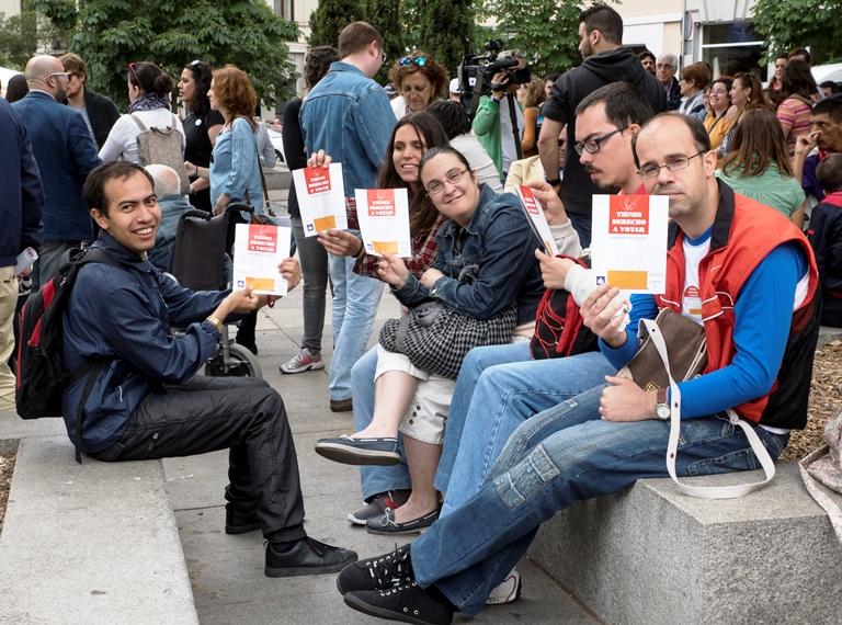 Un grupo de personas muestran un papel a favor del voto para todos