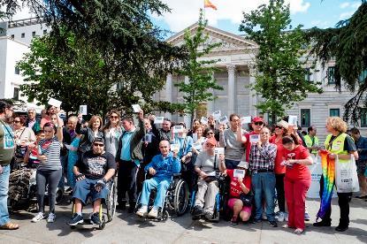 Un grupo de personas muestran un papel a favor del voto para todos con el Congreso de los Diputados de fondo