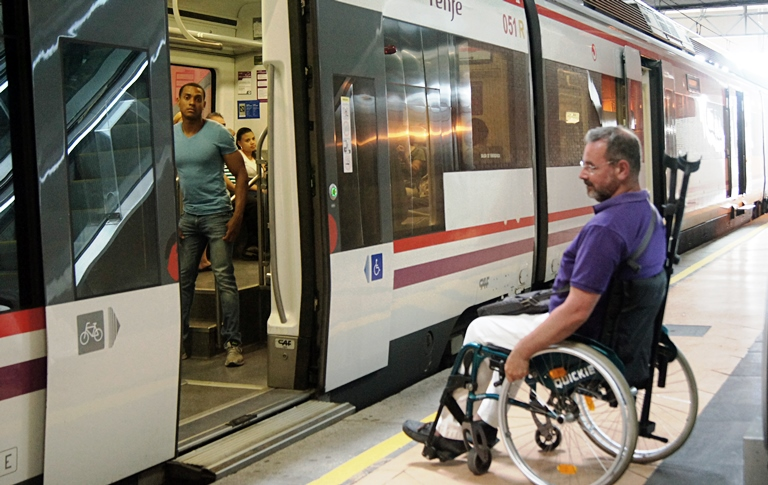 Un hombre en silla de ruedas en una estación de tren de cercanías