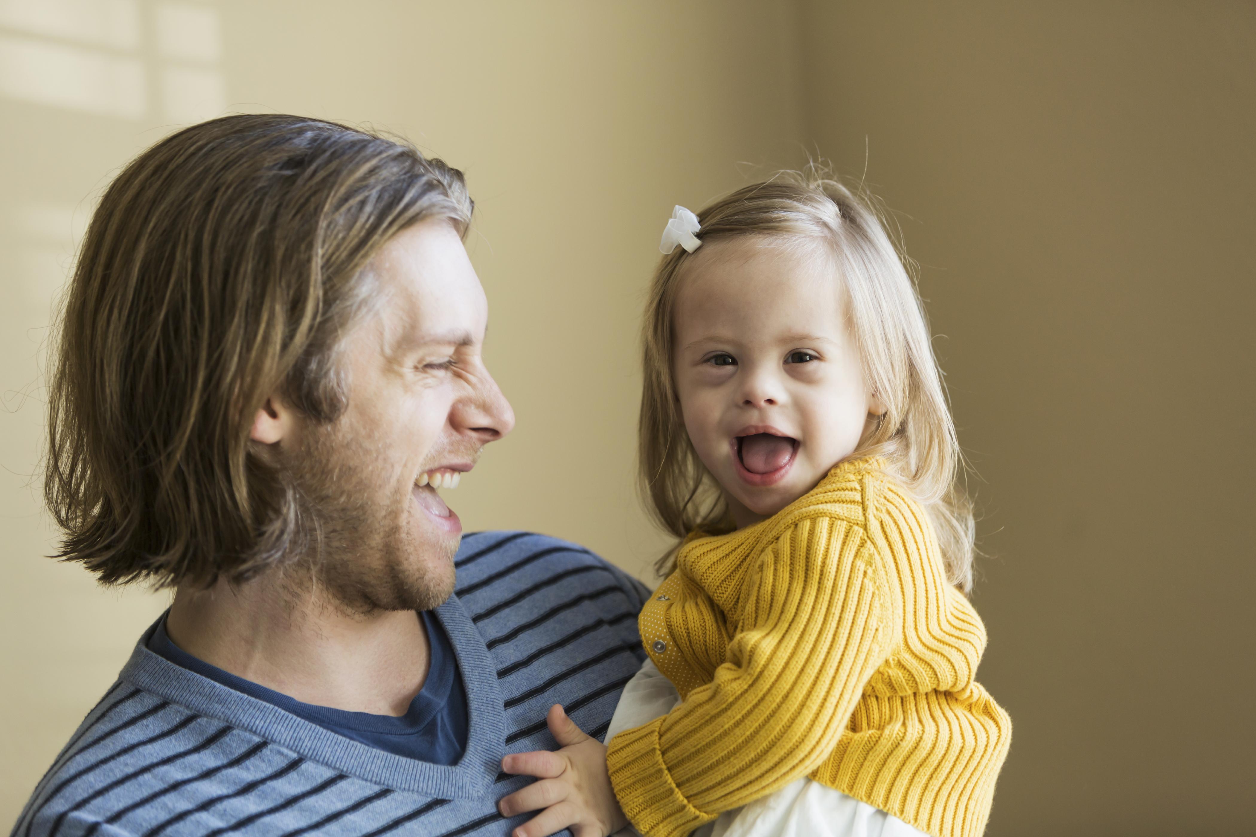 Padre sonriendo con su hija con síndrome de Down en sus brazos