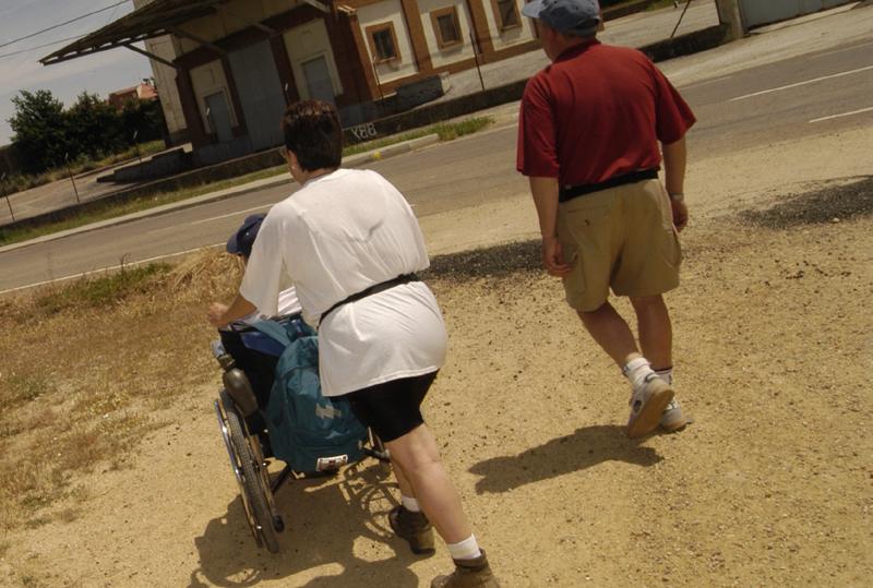 Una pareja acompaña a una persona con discapacidad