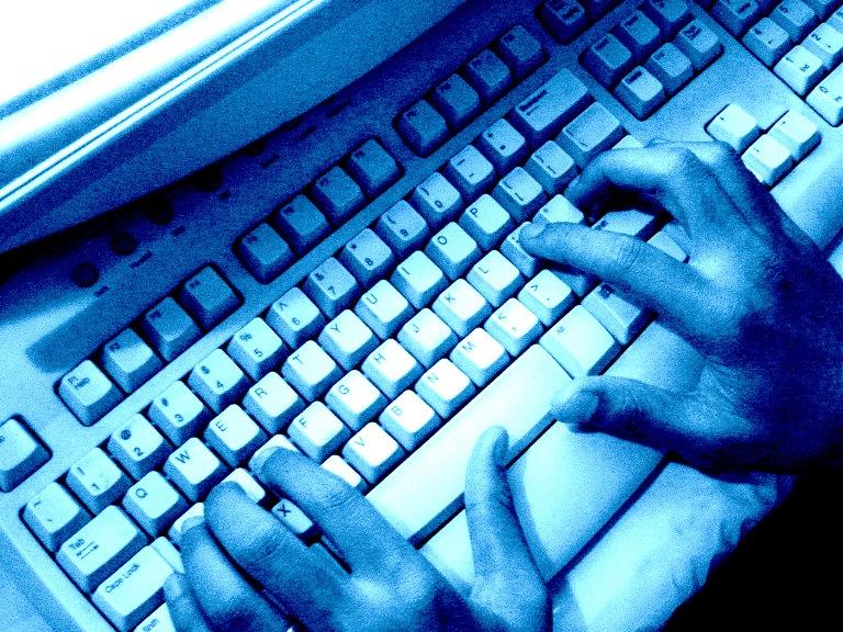 Teclado de ordenador y manos escribiendo
