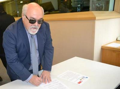 Yannis Vardakastanis, presidente del EDF, firmando la adhesión