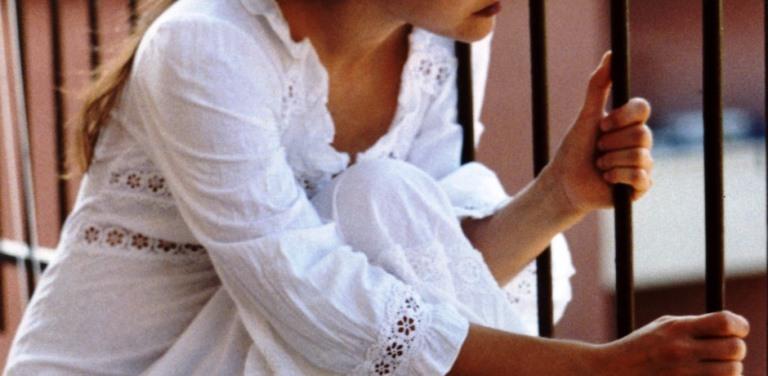 Una chica apoyada en una reja