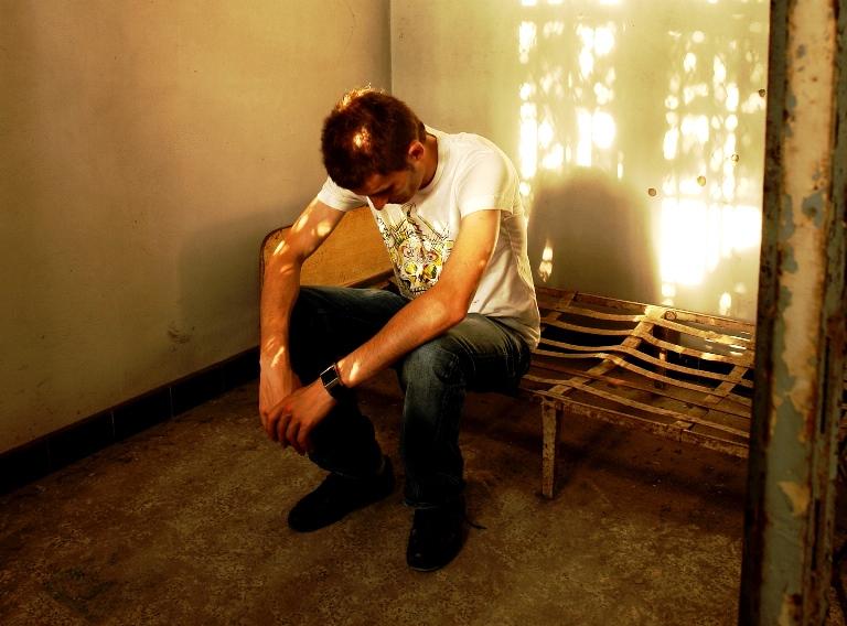 Un joven sentado en una celda de un manicomio