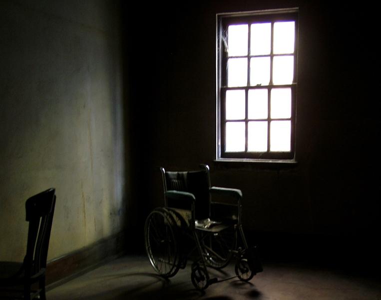 Ventana, desde el interior, de un psiquiátrico y una silla de ruedas delante de ella
