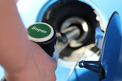 Detalle de una mano echando gasolina en el coche