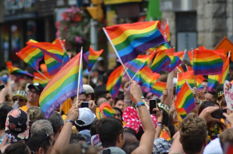 Imagen de un desfile del orgullo con banderas arco iris