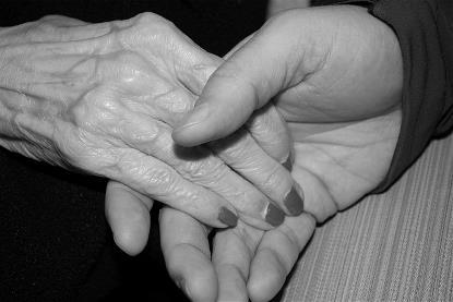 Mano de anciana sostenida por otra más joven