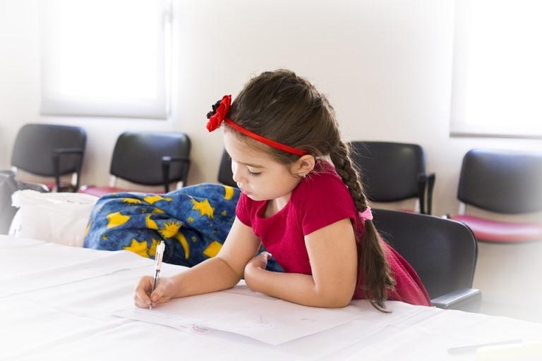 Una niña escribiendo sola en algún despacho de un colegio