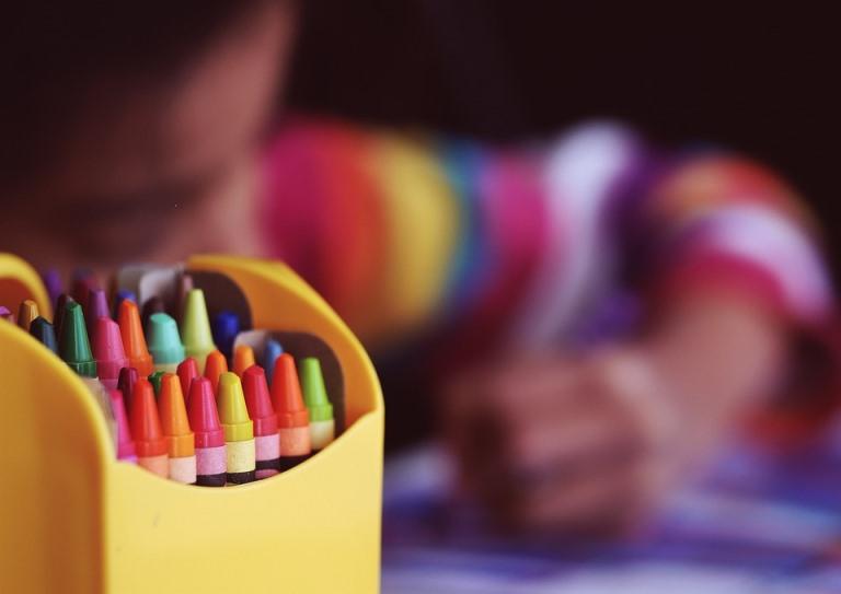 Imagen de una caja de ceras de colores y un niño desenfocado detrás