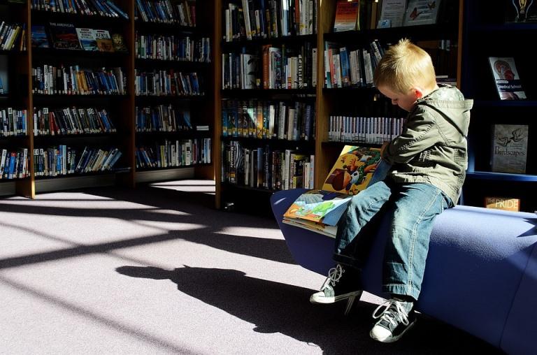 Un niño leyendo y sentado en la biblioteca de un colegio
