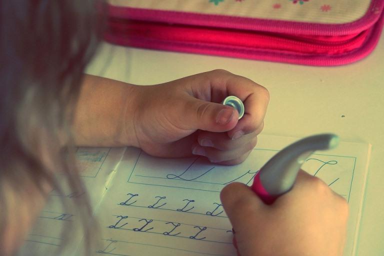 Una niña aprendiendo a escribir la letra z