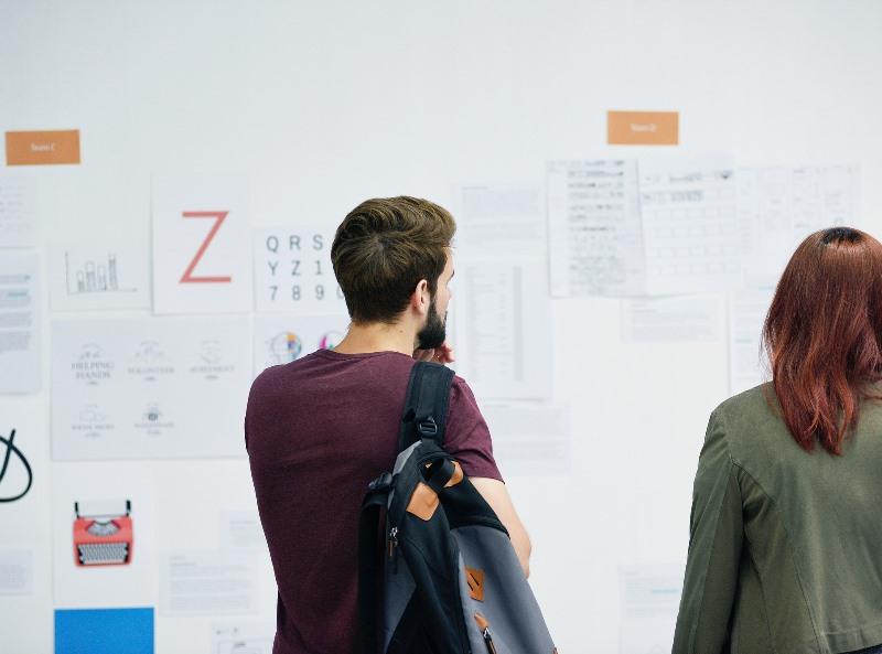 Dos personas mirando un tablón de anuncios