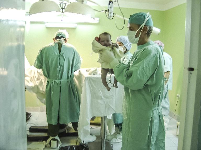 Un médico con un bebé recién nacido entre sus manos