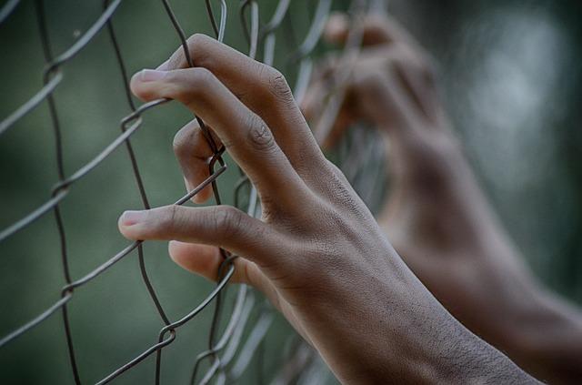 Unas manos agarradas a unas rejas