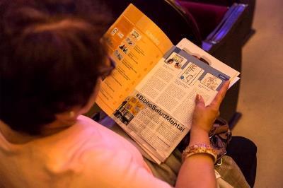 Una espectadora leyendo la revista Encuentro de Con Salud Mental España