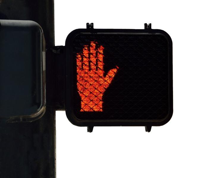 Señal de semáforo con una mano roja dando el alto