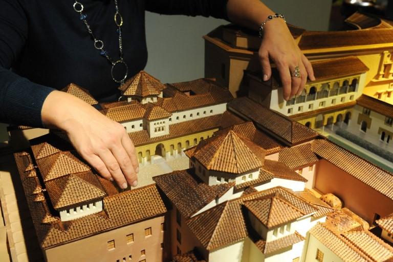 unas manos tocando la maqueta del Patio de los Leones de la Alhambra en el Museo Tiflológico