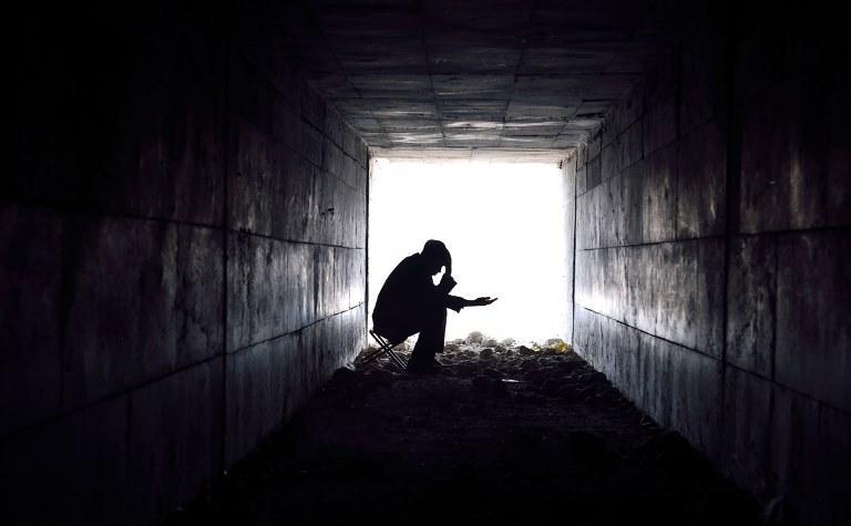 Un hombre pide limosna en la entrada de un túnel