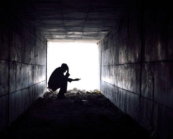 Detalle de un hombre en sombra pidiendo limosna a la entrada o salida de un túnel