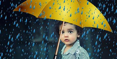 Un niño se protege bajo un paraguas