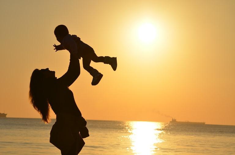 Perfiles a contraluz de una mujer y su hijo o hija en el momento de la puesta de sol