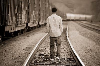 Adolescente caminando entre las vías del tren