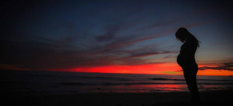 Perfil de una mujer embarazada en una playa, durante la puesta de sol o antes del amanecer