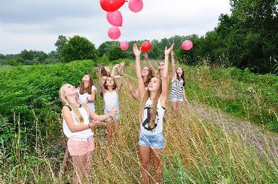 Grupo de niñas en el campo lanzando globos rojos