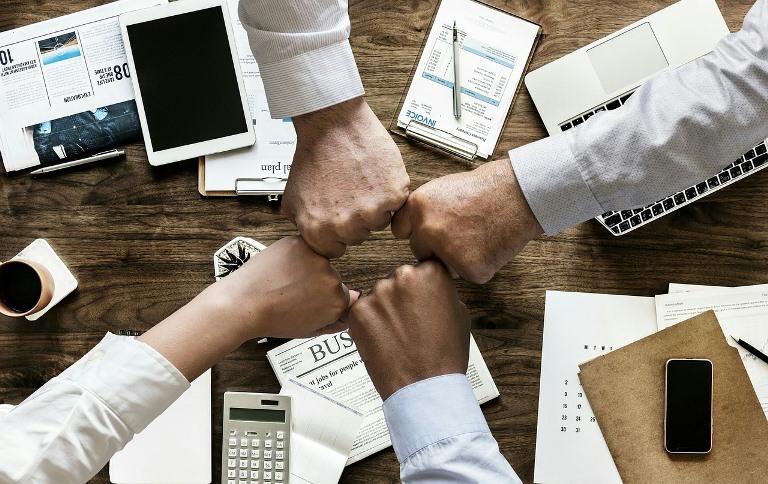 Manos de personas de negocios que se unen en apoyo unos de otros