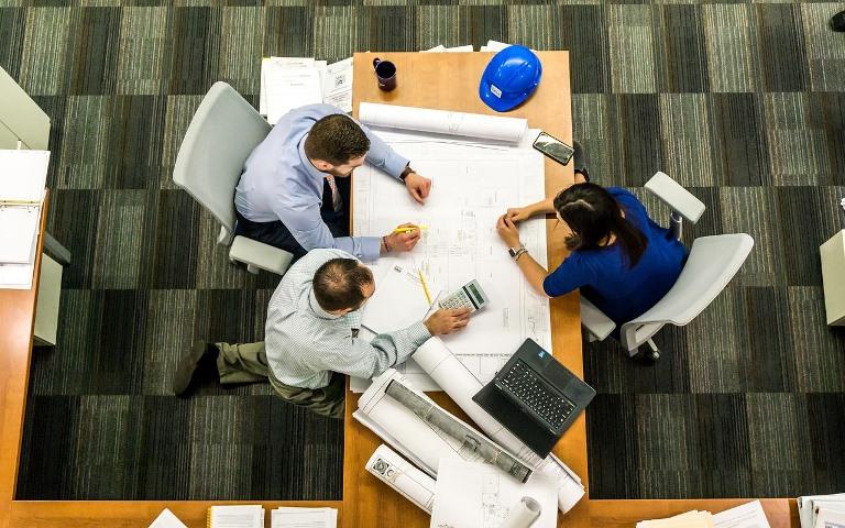 Varias personas trabajan sobre una mesa
