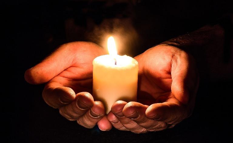 Manos sustentan una vela
