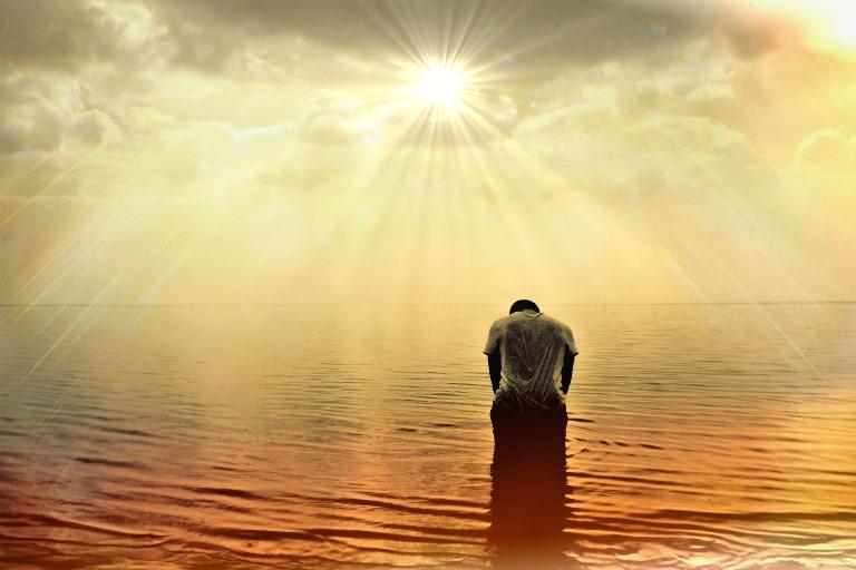 Persona postrada ante el sol sobre el horizonte