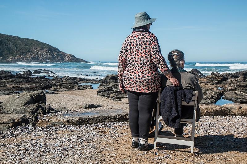 Una mujer acompaña a otra en silla de ruedas