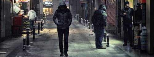 Imagen de una persona paseando sola por una ciudad en la noche