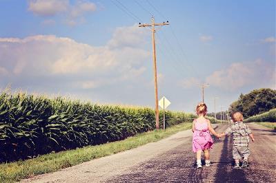 Dos niños de la mano se alejan por un camino rural