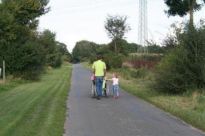 Hombre empuja una silla de ruedas acompañado de una niña por una carretera rural